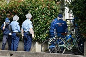進藤遼佑君の遺体が見つかった自宅のある集合住宅に入る捜査員=18日午前、さいたま市見沼区