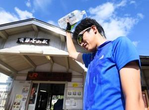 最高気温が40度を超えた岐阜県下呂市の飛騨金山駅前で、ペットボトルの水を浴びる男性=8日午後