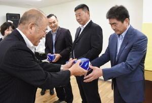 肥前びーどろをプレゼントする秀島市長(左)と連雲港市の代表団=佐賀市役所