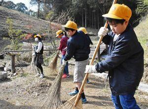竹ぼうきなどを使って清掃する児童ら=佐賀市久保泉町の帯隈山