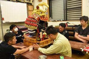 「上杉謙信の兜」のミニ曳山を修復する平野町の関係者たち=唐津市の平野町公民館