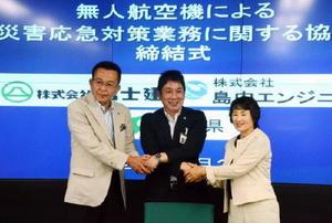 協定書への署名後、握手を交わす佐賀県の副島良彦副知事(中央)と富士建の牧薗博文社長(左)、島内エンジニアの島内きみ子社長=県庁