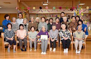 デイサービス利用者や職員と一緒に、記念写真に納まる田代ハヤさん(前列中央)=小城市芦刈町の芦刈保健福祉センター