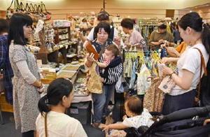 1着ずつじっくり見ながら子ども服を選ぶ来場者=佐賀市文化会館イベントホール