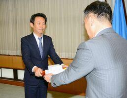 峰達郎市長(右)に防犯ブザーを渡す唐津地区遊技業組合の新冨和紀組合長=唐津市役所