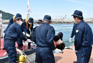 救助者を搬送する唐津署の署員たち=唐津市二タ子の佐賀県ヨットハーバー