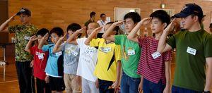 自衛隊員と敬礼をする子どもたち=吉野ヶ里町の陸上自衛隊目達原駐屯地