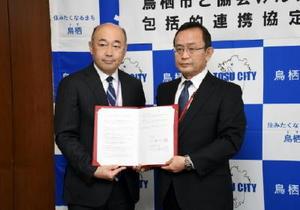 協定書を手にする橋本康志市長(左)と久米勝士・協会けんぽ佐賀支部長=1月11日、鳥栖市役所