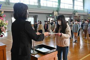 生徒を代表して永原里美校長(左)から修了証書を受け取る5年の市丸愛妃菜さん=佐賀市の川上小