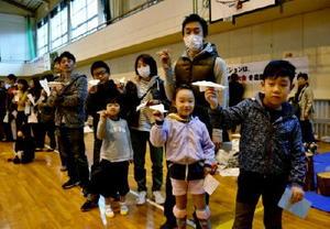 さあ飛ばすぞ。自作の紙飛行機を手に参加者たち=唐津市の唐津第五中体育館
