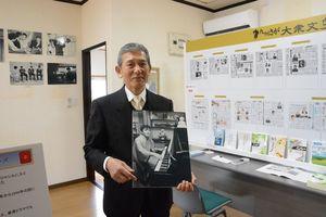 笹沢さんが自宅でくつろぐ写真を手にする島ノ江館長=佐賀市富士町小副川の笹沢左保記念館