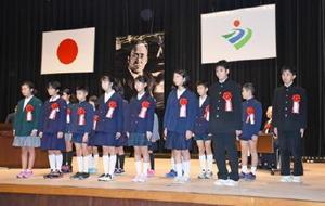 式典で、吉田絃二郎の遺影が掲げられた壇上に立つ読書感想文などの最優秀賞の児童生徒=神埼市中央公民館