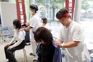 体験者に8分間の肩マッサージをする盲学校の生徒=佐賀市天神のアバンセ