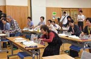 講座の中で「いすつかまりスクワット」を実践する参加者たち=佐賀市の西与賀公民館