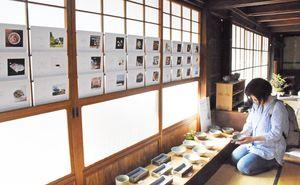 川口武亮さんの作品を手に取る来場者。引き戸にはみち草サンドウィッチ展の作品が並ぶ=唐津市北波多の草伝社