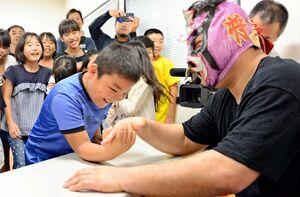 レスラーの将火怒さん(右)に腕相撲を挑む子どもたち=鹿島市音成の海道しるべ