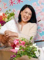 初当選が確実となり、花束を手に笑顔を見せる一ノ瀬裕子さん=7日午後10時28分、佐賀市水ケ江の事務所