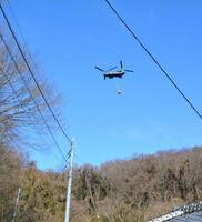 栃木県足利市の山林火災で、消火活動に当たるヘリコプター=27日午前9時21分