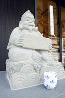 2斤分の食パンを両手で抱えたスタイルが特徴的な「銀座に志しかわ佐賀中央店」の恵比須像=佐賀市新中町