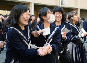 張り出されたボードに番号を見つけ、喜び合う受験生たち=佐賀市の佐賀西高