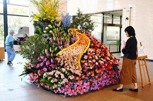 県産の花を使ったフラワーアレンジ。聖火リレーの道を表現している=県庁の県民ホール