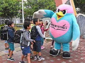 ウィントスに笑顔であいさつする児童たち=沖縄県の喜名小学校