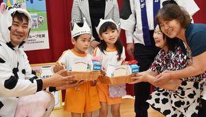 園児の代表に牛乳をプレゼントする県酪農婦人部連絡協議会の原口眞里子会長(右から2人目)ら=佐賀市の新栄保育園