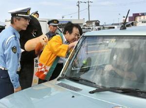 ドライバーに伊万里ナシなどを配り、交通安全をアピールする塚部芳和市長(右)と鶴直人署長ら=伊万里市二里町