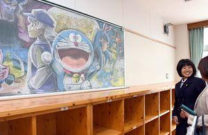 迫力ある黒板アート作品を見ながら、笑顔を見せる新入生たち=佐賀市の佐賀北高校