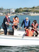 竹崎カニの供養祭後、カニを放流する関係者=太良町の竹崎港沖