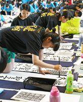 真剣な表情で筆を握り、揮毫(きごう)する生徒=小城市の芦刈文化体育館