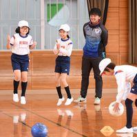 サガン鳥栖のスクールコーチに、正確なボールのけり方などを教わり実践する三田川小の児童たち=吉野ヶ里町の同校
