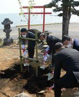 聖火リレーを記念した桜の苗木を植える参加者=太良町の大魚神社の海中鳥居前