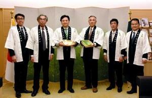 県アスパラ部会の山領敏正副部会長(左から2人目)と井手元博副部会長(右から3人目)からアスパラガスを受け取った山口祥義知事=佐賀市の県庁