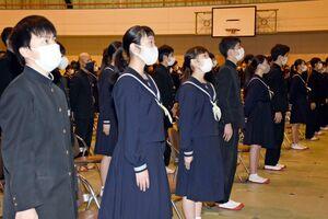 間隔を空けつつ、マスク姿で校歌斉唱する卒業生たち=唐津市の第五中学校