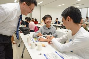 伊藤悦朗教授に見守られ、ノギスで腕の感覚を調べる生徒たち=佐賀市青少年センター