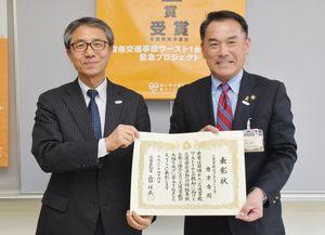 落合裕二県民環境部長(左)から、交通事故減少率ベスト1の表彰を受けた峰達郎市長=唐津市役所