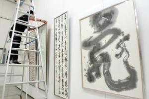 大賞など優秀作を見やすく飾り付けるスタッフ=佐賀市の県立美術館