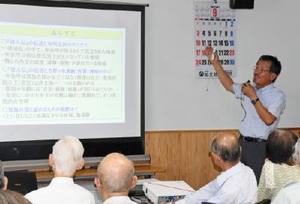 吉野ケ里遺跡について講演する七田館長(右)=佐賀市の商工ビル