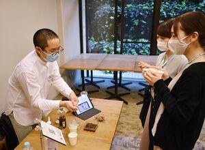 シオマネキを塩で熟成させた珍味「蟹漬(がんづけ)」について、「手作りの道具を使って捕まえる」などと説明する竹下商店の三木雄太専務(左)=佐賀市の県庁
