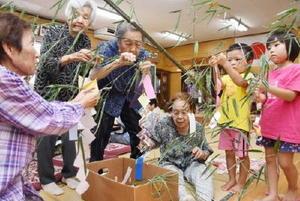 竹に飾り付けをする地域サロンメンバーと伊福保育園の園児たち=太良町の伊福集会所