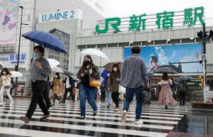 マスクを着用してJR新宿駅前を歩く人たち=13日午後