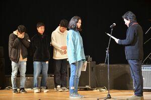 進藤健介審査委員長(右)から表彰を受ける来島エルさん。左後方は浜崎音楽少年団のメンバー=唐津市民会館