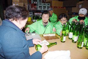 瓶詰めが終わった日本酒にラベルを貼る地酒プロジェクトのメンバーら=みやき町の天吹酒造