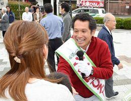 街頭演説に集まった人たちと握手を交わす大串博志候補=伊万里市のJR伊万里駅前