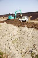 1年余り雨にさらして潮抜きした潟泥をダンプに積み込む=鹿島川の河川敷