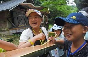 お手製の竹箸と器でそうめん流しを楽しむ児童=佐賀市の北山少年自然の家