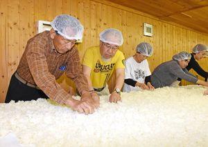 蒸した米を薄く広げ米こうじを作る作業に取り組む参加者=みやき町の天吹酒造