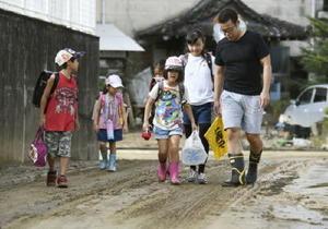 保護者に付き添われ、泥の残る道を登校する福岡県朝倉市立大福小の児童たち=10日午前