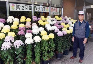 「花の形や色、艶を見てほしい」と話す菊作り教室講師の時田義光さん=みやき町の鳥栖・三養基西部リサイクルプラザ